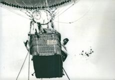 Aviatik, woman shoveling out sand to get air balloon to fly.