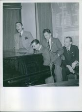 Men siting together, playing piano.