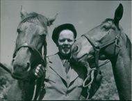 Man standing with horses, holding snaffles.