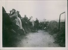 Soldiers taking position in the trench and looking at the enemies through binoculars.