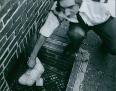 Karl Paulsch putting a plastic bag in the sewer, 1972.