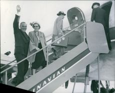 Man and woman waving and boarding an aircraft.