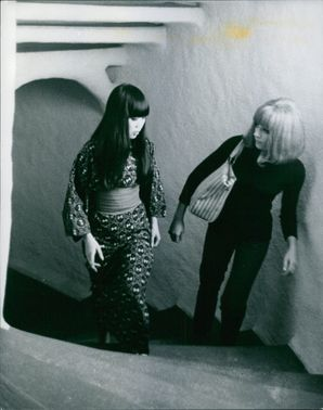 Two women stepping up staircase.  November 15, 1967