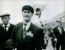 Close up of a man at the railway platform with other people. 1966