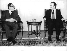 Henry Alfred Kissinger sitting in a chair with President Hafez el Aaeed of Syria.