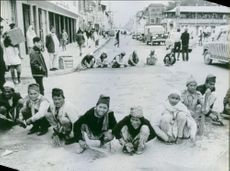 People gathered on street, sitting together and looking towards the camera in Nepal.