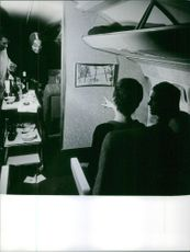 Men and women in the airplane, while the servicewoman serving drinks.