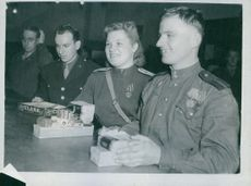 A Russian girl officer and her young be-medalled companion smile as they receive their rations of 200 American in the courthouse in Nuremberg. 1945