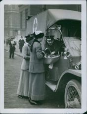 A soldier riding a vehicle checks a basket the two women him on the street, 1915.