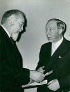 Swedish author Alf Henriksson receives the prize amount of 25,000 SEK by author Carl Emil Englund.
