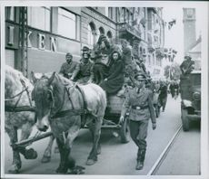 Military men and women rides a carriage through the street in a town during the war, 1945.