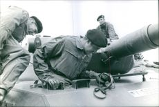 Juan Carlos in Bonn inspecting meticulously  on an item beside a cannon together with two German soldiers.   1972
