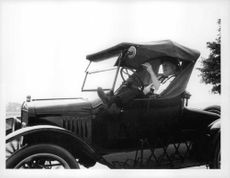 Man relaxing in Ford Model T.