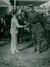 Two men personalities shaking hands during Olympics.