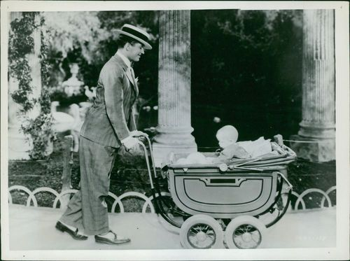Maurice Chevalier with baby trolley.