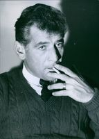 Portrait of  an American composer, conductor, author, music lecturer, and pianist Leonard Bernstein smoking. 1959