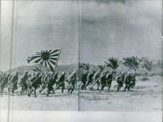 A large number of soldiers run across the field while carrying their rifles and a flag in Japan during the war, 1964.