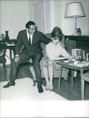 Vittorio Gassman sitting with woman.