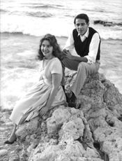 Lamia Solh and Prince Moulay Abdellah of Morocco, sitting on the rocks by the beach.