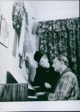 Einar Beyron playing a piano while Brita Hertzberg listening to him, 1945.