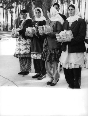 Women in Iran holding a pile of papers.