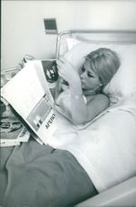 Sandra Milo lying on bed in hospital and reading magazine.