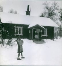 Man and a woman looking at a girl standing on snow capped field. Photo taken 1948