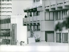 People standing in the balcony of the building.