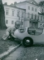 A little boy pushing his car in garden.