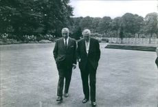 Former British Prime Minister Harold Wilson is discussing with former French Prime Minister Georges Pompidou, both of them are walking