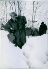 A soldiers carrying a bag while walking in the snow during the Norwegian Campaign, 1940.