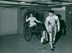 Eddie Barclay holding the chariot while his wife inside of it.1964.