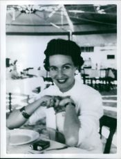 A woman siting in the restaurant and smiling.