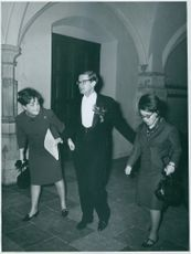 Princess Margriet of the Netherlands and his spouse Pieter van Vollenhoven with a woman, walking in a hallway, smiling, in 1966.