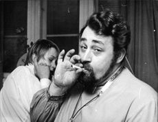 Cornelis Vreeswijk smoking a cigarette, with a boy behind him, covering his ears, 1968.