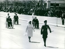 A military officer marching on the street, with women in white uniform, pushing the men in wheelchair.