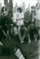 Group of people burying something to the ground.