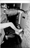 Policemen use hydraulic tools to break up the door in the apartment