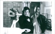 Eddie Murphy with Bronson Pinchot, looking at something and smiling during a scene in film Beverly Hills Cop.