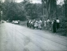People gathered on the roadside. 1960