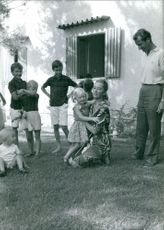 Queen Paola of Belgium playing with children in lawn.