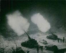 A picture just released by the U.S. Department of Defence showing artillerymwn firing Long Tom guns in support of infantry somewhere in KOREA. The flashed illuminationg the snow-covered ground are reminiscent of the two London blitz barrage in 1940.