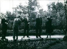 King Gustaf V standing with three men and a woman looking at something.