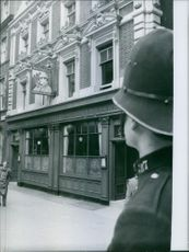 A guard looking towards building. 1959