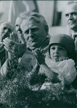 Antonin Josef Novotny sitting and clapping with a child.