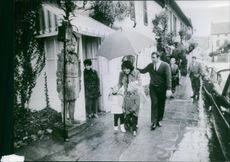 Madame Nguy?n Cao K? fiance of Nguy?n Cao K? former vice president of Vietnam going somewhere with her child during rain, an official hold a umbrella to their overhead