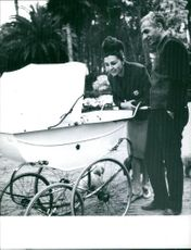 Man and woman looking in baby cart.