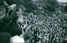 Infante Juan of Spain standing on balcony and looking at crowd gathered in front of home. 1967