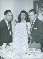 Felix Alvo standing with man and woman. 1958