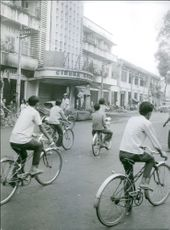 People cycling in street and looking at the ruined building.1963